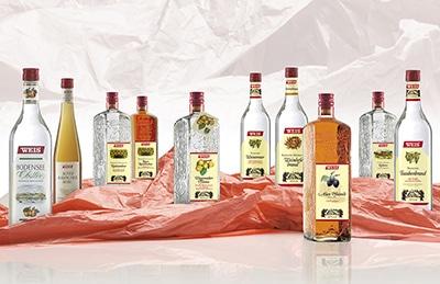 10 Flaschen Süddeutsche Brennerei Spezialitäten stehen locker aufgereit nebeneinander auf rotem zerknittertem Seidenpapier.alt attr für Spirituosen, Flaschenfotograf, Getränke Fotografie, Getränkefotograf, Getränkefotografie