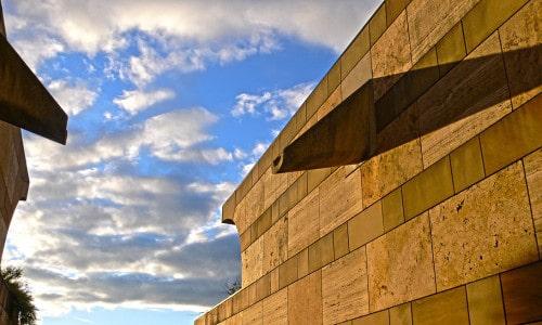 Tiefer Sonnenstand und bewölkter Himmel an der Staatsgalerie Stuttgart. Eine Weitwinkelaufnahme vom Durchgang zeigt die golden braunen Travertin Wände rechts und links.