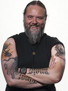 Studio Portrait vom tätowierten Frontmann Andreas von der Heavy Metal Band Vikingsmusic Stuttgart. Sein schwarzes T-Shirt ist hochgeschoben, um die Tattoos auf den Armen besser zu sehen. alt attr. für Fotograf, Kundenmeinung, gelungenes Shooting