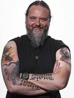 Studio Portrait vom tätowierten Frontmann Andreas von der Heavy Metal Band Vikingsmusic Stuttgart. Sein schwarzes T-Shirt ist hochgeschoben, um die Tattoos auf den Armen besser zu sehen.