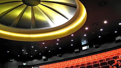 Die Architektur eines altes Lichtspielhauses in Stuttgart mit roten, aufsteigenden Sitzreihen und einem riesigen, stilisierten, gelblich beleuchteten Ablüfter an der Decke. alt attr - Produktfotografie. Fotostudio Herb Allgaier, Fotograf