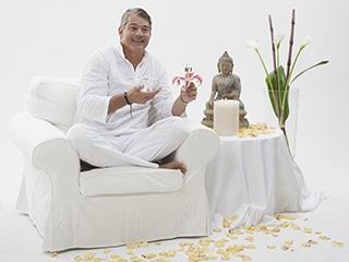 Ein Yogalehrer im Seminar sitzt im Schneidersitz auf einem weissen Sessel auf der Bühne und hält ein Yoga Seminar ab - in der Hand hält er eine Lotusblüte.