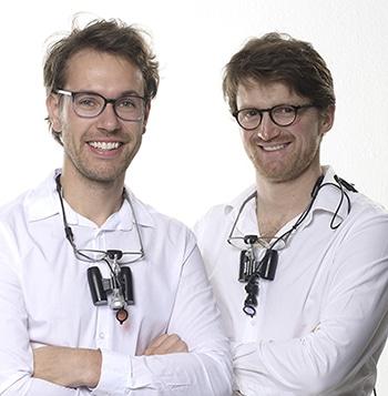 Dr. Leonhardt und Dr. Haug. Zwei junge Zahnärzte in weiss vor weiss mit um den Hals hängenden Lupenbrillen und verschränkten Armen lächeln zur Kamera.