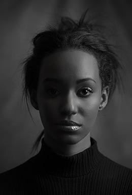 frontales Schwarzweiss Portrait einer Afrikanerin mit hochgestecktem Haar, schwarzem Rollkragen vor dunklem Hintergrund im stimmungsvollen Seitenlicht. alt attribute für: Fotomodel,Black Beauty,