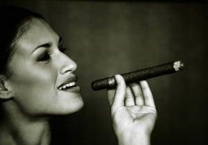 Eine rassige Brasilianerin im Profil mit einer Zigarre zwischen den Fingern und einem zufriedenen Lächeln auf den Lippen.